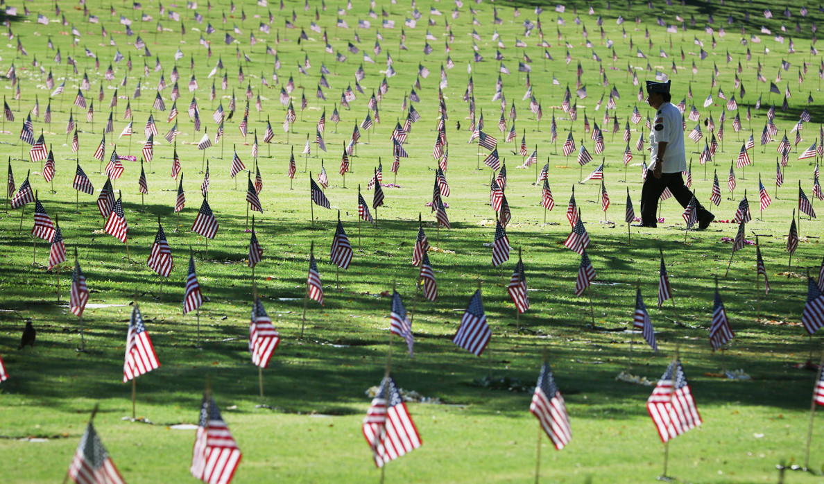 Flags decorate the graves of fallen service members who died in conflicts dating back to World War I.