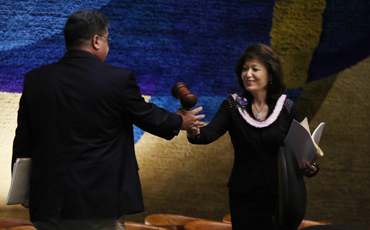 Sen. Donna Mercado Kim hands the gavel to Sen. Ron Kouchi after their colleagues voted to shake up the Senate leadership late in the session.