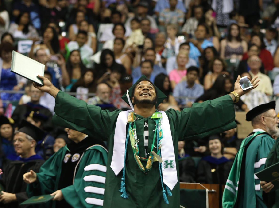 A diploma in one hand and a cell phone in the other, DiQuinton Pedroza exults after graduating.