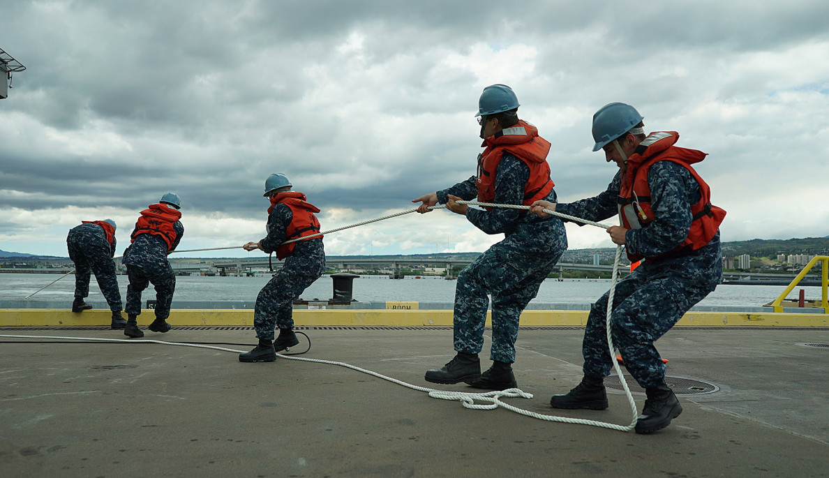 Navy personnel pull in lines from the carrier, which was making a brief stop in Hawaii before returning to its home port in San Diego.