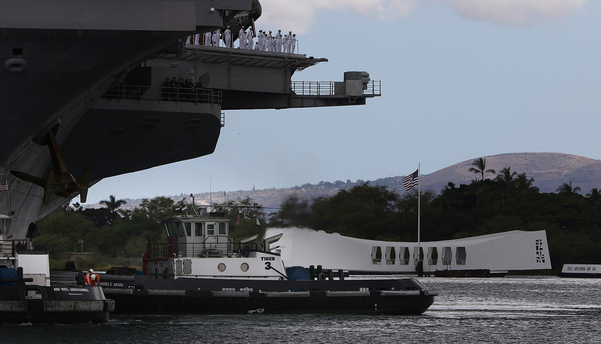 Crew members on the deck check out the USS Arizona Memorial as their vessel arrives in Pearl Harbor.