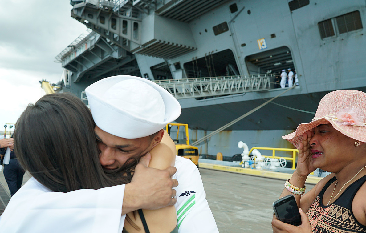 Crew member Keanu Robertson of Hawaii, an aviation boatswain's mate equipment airman, hugs his girlfriend, Amber Eckerle, as his tearful sister, Mia Nina Turro, watches.