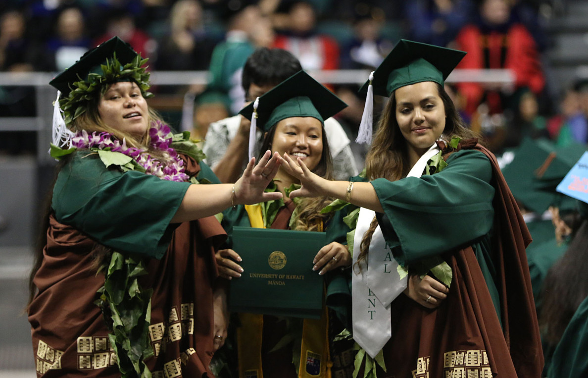 Students pose for a photo with one of their diplomas front and center during commencement.