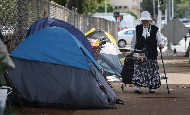 An elderly woman walks past tents located along Beretania Street across from Aala Park. 4 june 2015. photograph Cory Lum/Civil Beat