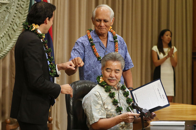 Representative Chris Lee and Senator Mike Gabbard bump their fists after Governor Ige signed each bill during bill signing ceremony held at the Governors office.  Governor Ige signed 4 bills into law.  8 june 2015. photograph Cory Lum/Civil Beat