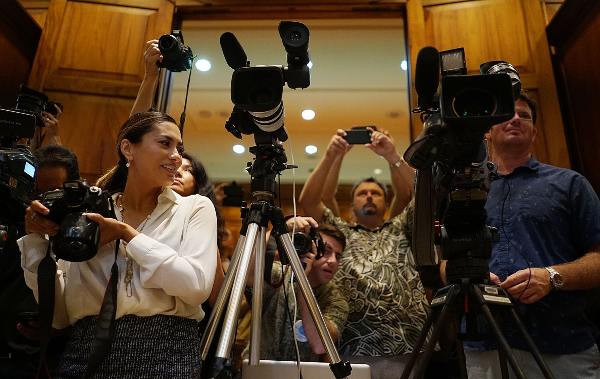 Yasmin Dar, left, Gov. David Ige's digital media specialist, was on hand for a bill-signing ceremony Monday. Dar is no stranger to reporters and photographers jostling for position at media events. She is a former TV reporter who went to work for Ige earlier this year.