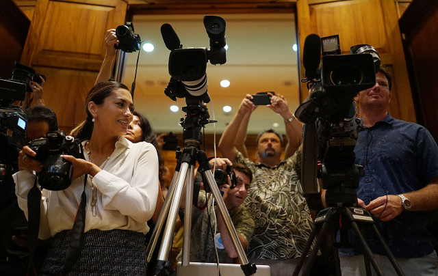 Yasmin Dar, left, Governor Ige's Digital Media Specialist looks on as photographers jostle for position during bill signing ceremony held at Governor's office at the Capitol.  8 june 2015. photograph Cory Lum/Civil Beat