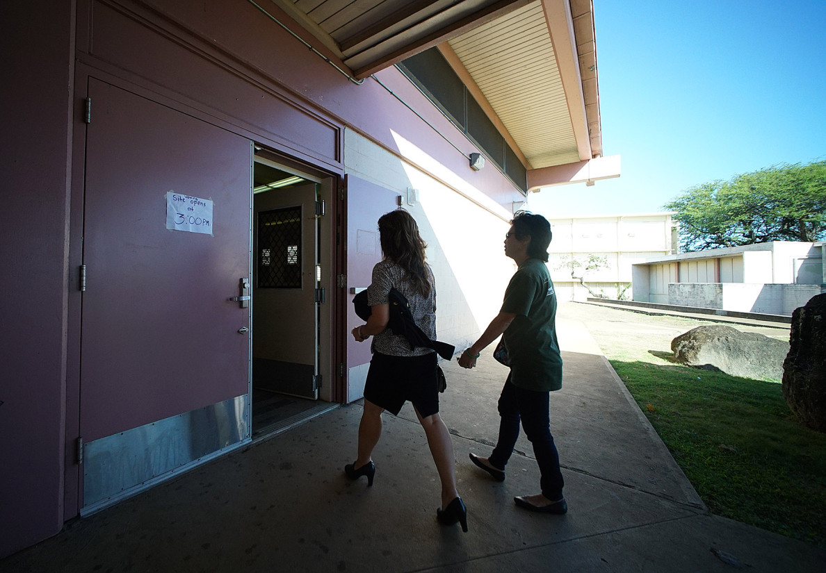 HSTA members head into the Farrington High School cafeteria to vote. The union election has been mired in controversy including a lawsuit by dissident candidates.