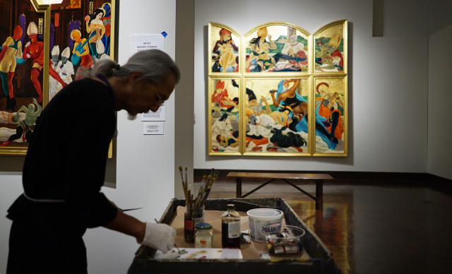 Masami Teraoka mixes some oil pigments while painting at the Honolulu Museum of Art. 25 june 2015. photograph Cory Lum/Civil Beat