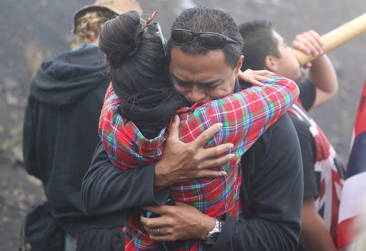 Kekoa Kaluhiwa, first deputy director of the state Department of Land and Natural Resources, embraces a demonstrator Wednesday. Even as they pushed to reopen the way to the Thirty Meter Telescope construction site on Mauna Kea, DLNR officials and officers commiserated with the people opposing the project's location on what some consider sacred ground.