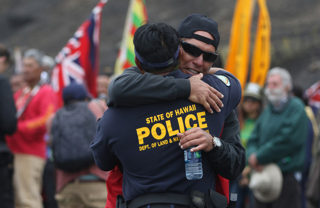 Mauna Kea supporter hugs DLNR law enforcement officer after announcing that the the DLNR was turn around and headed back down to regroup. 24 june 2015. photograph Cory Lum/Civil Beat