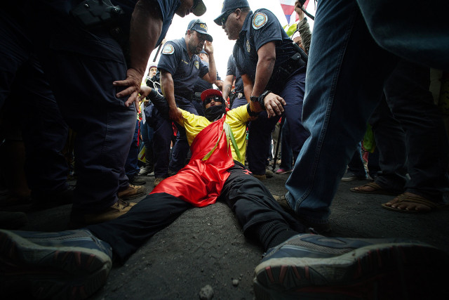 Law enforcement officers arrest a protester on Mauna Kea.
