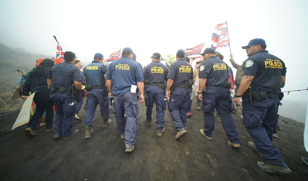 DLNR officers ask demonstrators to move out of the way of vehicles attempting to ascend from the Mauna Kea visitor center.