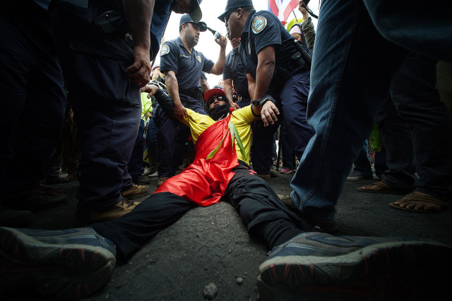 TMT demonstrator lays on the ground being cuffed with plastic restraints and refusing to move out of the DLNR motorcades movement up the Maunkea Observatory access road as hundreds of anti TMT and protect Maunakea demonstrators slowed the movement of the DLNR motorcade from the Maunakea Visitors Center. 24 june 2015. photograph Cory Lum/Civil Beat