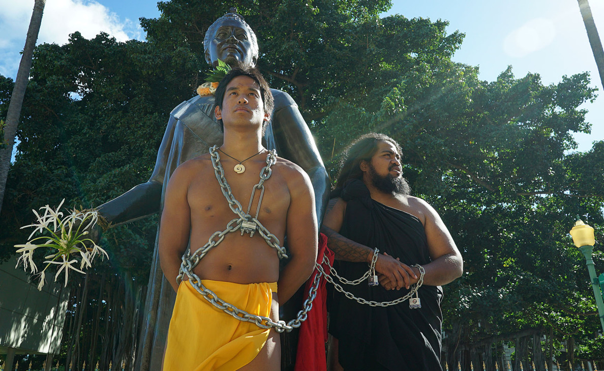 Kainoa Keanaaina, left, and Kaipo Hanakahi drew a slew of curious visitors interested in their protest, which kept them chained to the Queen Liliuokalani statue for several hours. The Native Hawaiian activists took great care to protect the statue from damage, wrapping a towel around places where the chains could scratch the bronze.