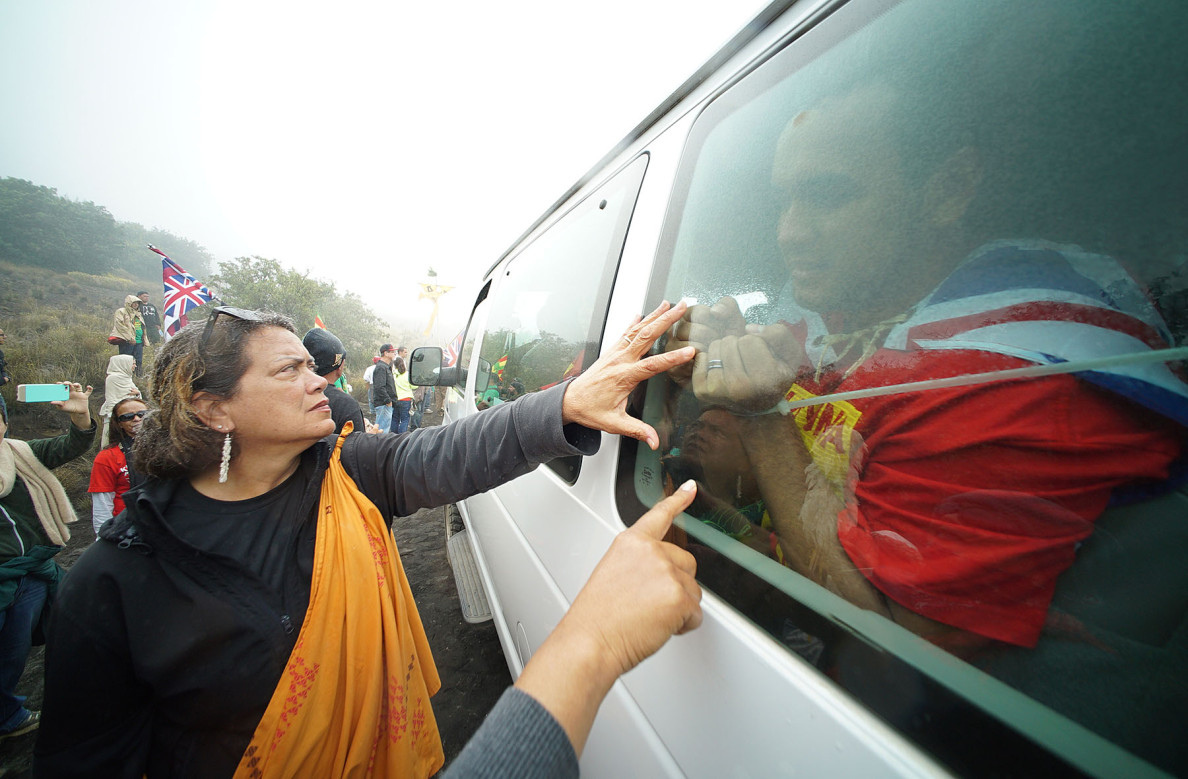 Protesters show their support for an arrested demonstrator by touching the window of the van he was placed in.