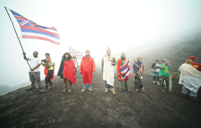 Demonstrators line the access road with clouds and rain chanting against the DLNR motorcade that was making their move up Maunakea. 24 june 2015. photgraph Cory Lum/Civil Beat