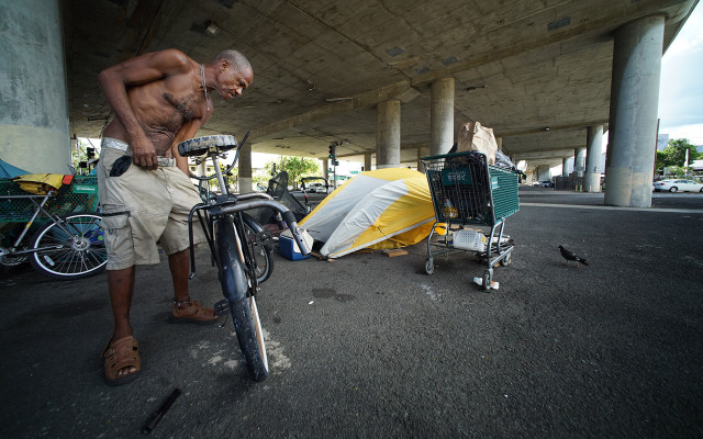 Oliver (only first name given) adjusts his bicycle near his tent under the H1 overpass, along Harding Avenue. homeless tents. 16 july 2015. photograph Cory Lum/Civil Beat
