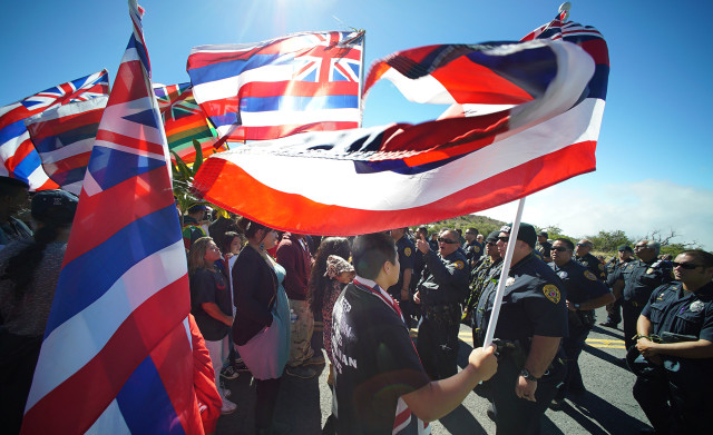 Mauna Kea demonstrators line the access road holding flags as DLNR law enforcement officers head up the mountain on foot. 24 june 2015. photograph Cory Lum/Civil Beat