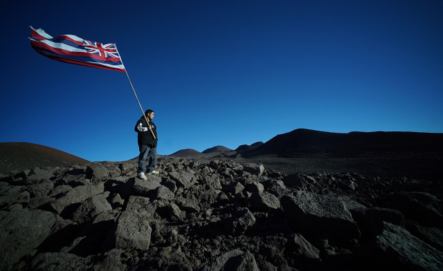 Lone demonstrator holds a Hawaiian flag near the summit of Mauna Kea as hundreds of protestors lined the road down at the visitor's center. 24 june 2015. photograph Cory Lum/Civil Beat