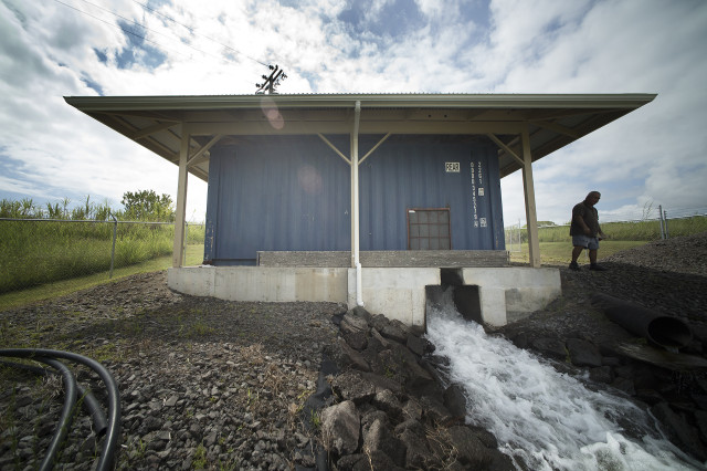 Hawaii island farmer Richard Ha stands near a small shipping container/structure that houses his water-powered turbine on his farm near Hamakua. Hamakua Springs. Hawaii. Peepeeko., photograph Cory Lum/Civil Beat