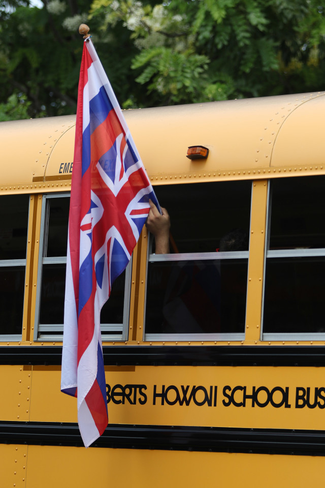 Aloha Aina march supporter holds their upside down Hawaiian flag as they arrive at Saratoga Road beginning of the march to Kapiolani Park. 9 aug 2015. photograph Cory Lum/Civil Beat
