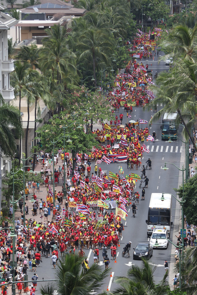 View from parking structure at thousands of Aloah Aina Unity march demonstrators holding flags along Kalakaua Avenue on their way to Kapiolani Park. 9 aug 2015 . photograph by Cory Lum/Civil Beat