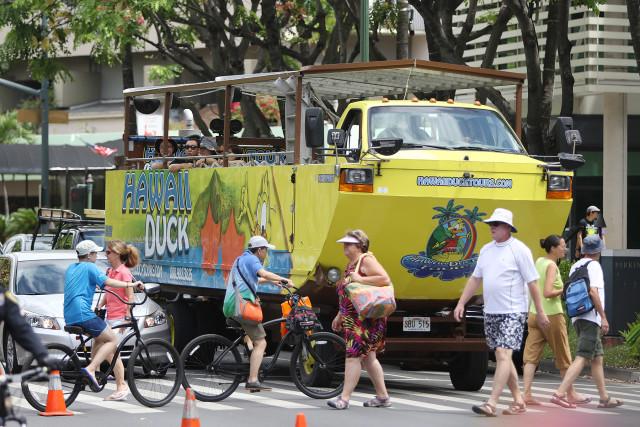 Hawaii 'duck' amphibious tour vehicle waits in traffic along Kalakaua Avenue. Tourism. HVCB. TOURIST. VISITORS. 9 aug 2015. photograph Cory Lum/Civil Beat