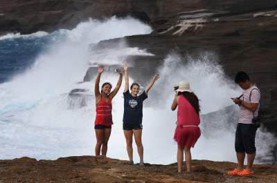 Visitors enjoy posing photographs at Lanai Lookout as large surf from tropical storm Guillermo, pounds the shoreline cliffs.  6 aug 2015. photograph Cory Lum/Civil Beat