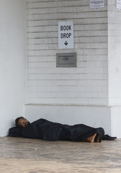 Person naps and stays dry under McCully-Moiliili Public Library as torrential downpours from remnants of tropical storm 'Kilo' passed south of the islands. 24 aug 2015. photograph by Cory Lum/Civil Beat