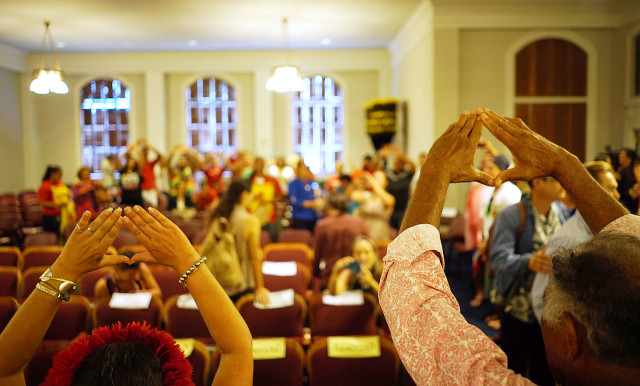 Supporters of Mauna Kea sing and hold up their hands representing the 'mauna' after oral arguments presented at the Hawaii State Supreme Court, Aliiolani Hale. 27 aug 2015. photograph Cory Lum/ Civil Beat