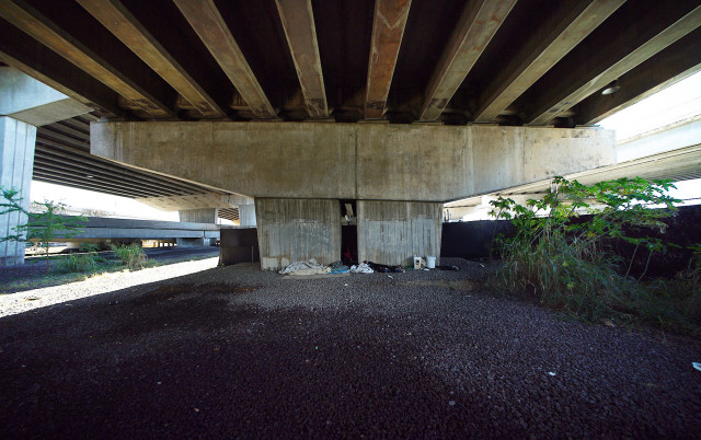Remnants of sleeping bags and other personal items sit under the Nimitz viaduct as hundreds of cars speed to Airport direction and cars head Honolulu bound oblivious to the denizens that make the underpass their home.  12 aug 2015. photograph Cory Lum/Civil Beat.