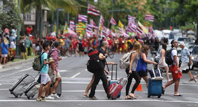 Visitors cross carrying luggage along Kalakaua Avenue as Aloha Aina Unity March demonstrators head down Kalakaua Avenue. 9 aug 2015. photograph Cory Lum/Civil Beat