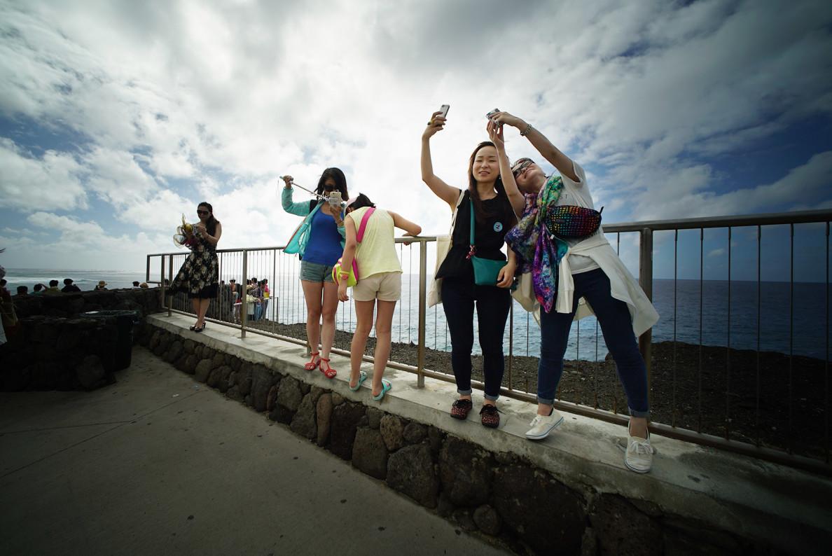 Visitors shoot selfies at the Halona Blowhole lookout.