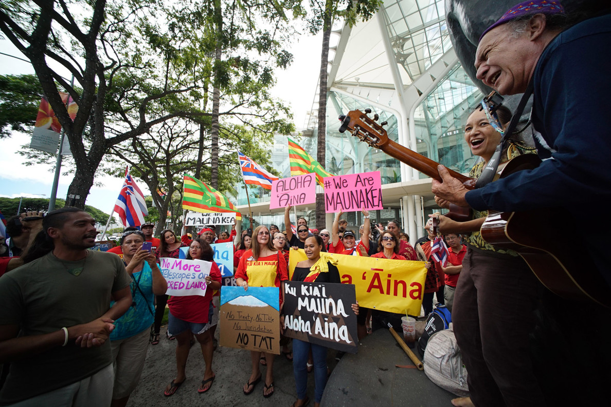 Demonstrators sing and hold signs fronting Hawaii Convention Center during IAU general assembly convention. 4 aug 2015. photograph Cory Lum/Civil Beat