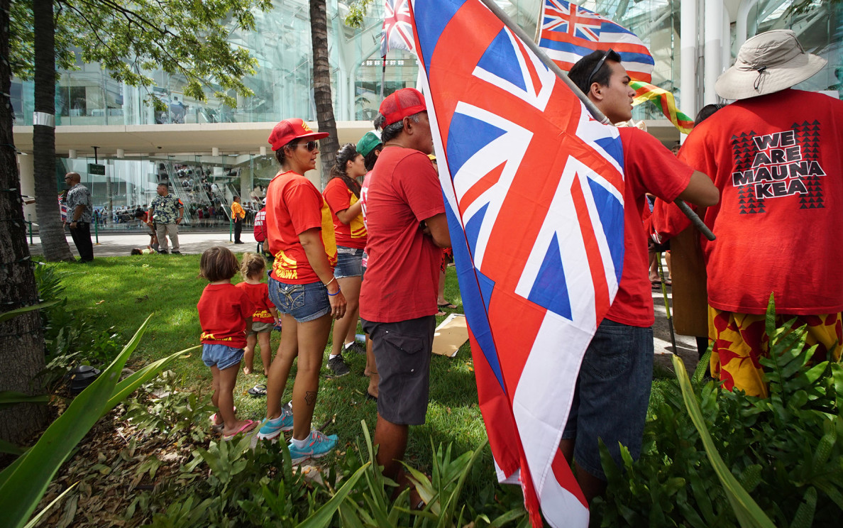 Demonstrators who oppose construction of the Thirty Meter Telescope on Mauna Kea stand outside the Hawaii Convention Center during the International Astronomical Union convention Tuesday.