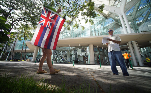 Kanani (declined last name) holds signs and a Hawaiian flag with other demonstrators fronting the Hawaii Convention Center during IAU general assembly convention. 4 aug 2015. photograph Cory Lum/Civil Beat