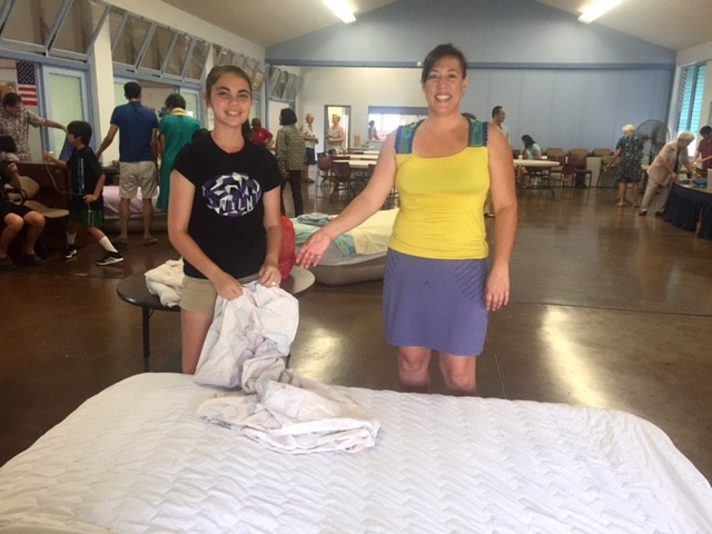 Volunteers Mary Sox-Pollard, left, and Terry Ogawa set up bedding for the homeless who slept at the Church of the Crossroads near the University of Hawaii for a week.