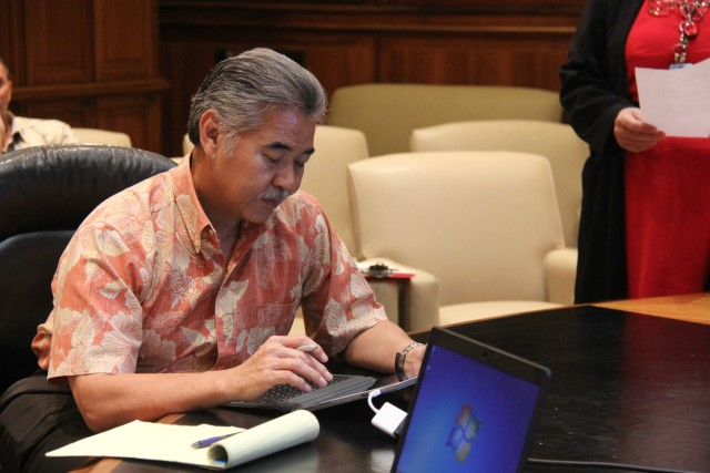 Gov. David Ige uses a tablet to sign documents electronically. The governor is a big proponent of going paperless.