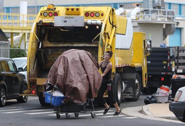 Person pushes grocery cart loaded with belongings after 11am as yellow trash truck showed up with city and county workers cleaning up garbage and belongings near Keawe and Ilalo Street in Kakaako. Homeless sweep. 21 sept 2015. photograph Cory Lum/Civil Beat