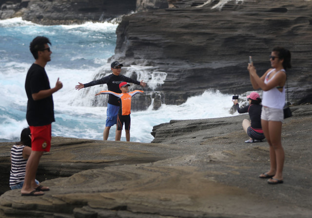 Visitors to Lanai Lookout hopped over wall, disregarding 'Danger' signs and pose for photographs on the gravel laden. sloped mountain side. 30 sept 2015. photograph Cory Lum/Civil Beat