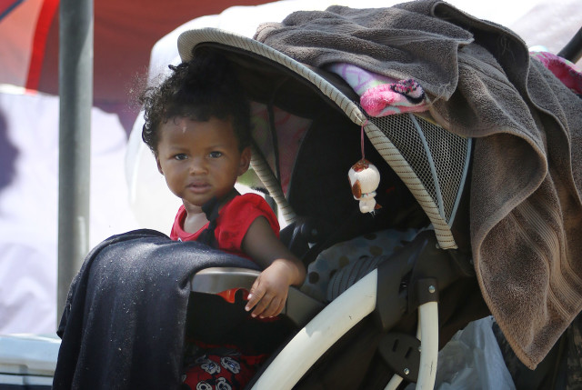 Baby waits in the stroller as mom assists a man with disassembling his tent along Cooke Street as City and County workers pick up trash along Ohe Street as part of the city's homeless cleanup in Kakaako. 8 sept 2015. photograph Cory Lum/Civil Beat