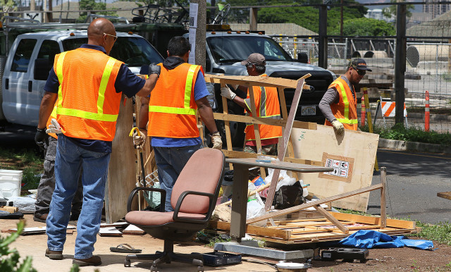City and County workers disassemble a wooden structure and load the wood into a trash truck near the intersection of Keawe Street and Ilalao Street. 17 sept 2015. photograph by Cory Lum/Civil Beat