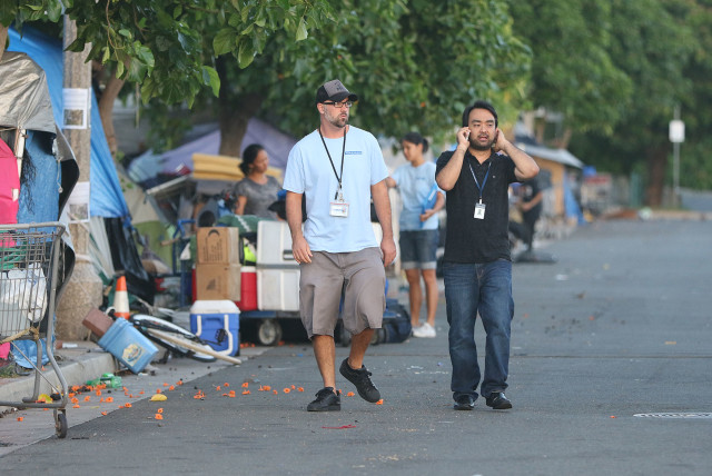 Scott Morishige, the governor's coordinator on Homeless, surveys the streets of Kakaako before Thursday's sweep.