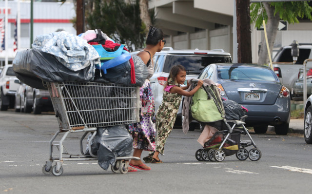 Families move their personal belongings on carts along Ahui Street as city workers sweep on Ilalo Street on Oct. 8.