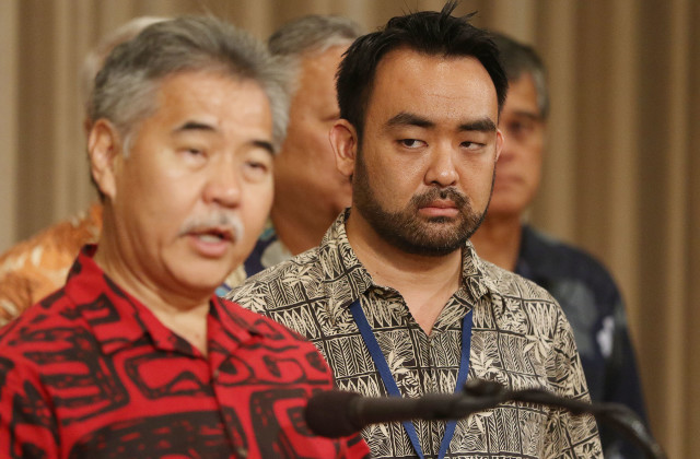 The state's coordinator on homelessness, Scott Morishige, listens to Gov. Ige during a press conference, October 2015.
