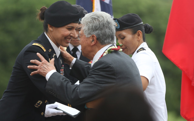 Congresswoman Tulsi Gabbard embraces Senator Daniel Akaka after oath portion of promotion ceremonies at the National Memorial of the Pacific. Punchbowl Cemetery. 12 oct 2015. photograph by Cory Lum/Civil Beat