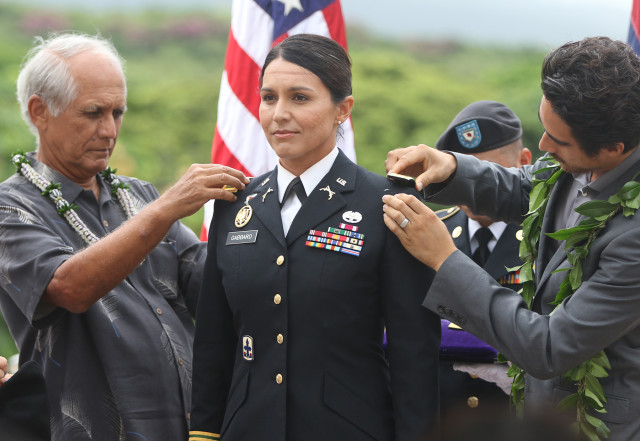 Senator Mike Gabbard and right, Abraham Williams place major rank on daughter/wife Congresswoman Tulsi Gabbard during ceremonies promoting Gabbard to a Major at the National Cemetery of the Pacific. Punchbowl Cemetery. 12 oct 2015. photograph by Cory Lum/Civil Beat