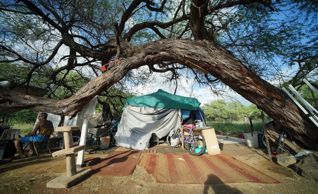 Jay sits in his camp area complete with falling kiawe tree.