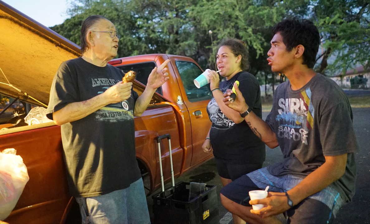 Eugene Muratsuka drives out from Pearl City every Saturday to share simple meals with people living in The Harbor like Kalani, right.